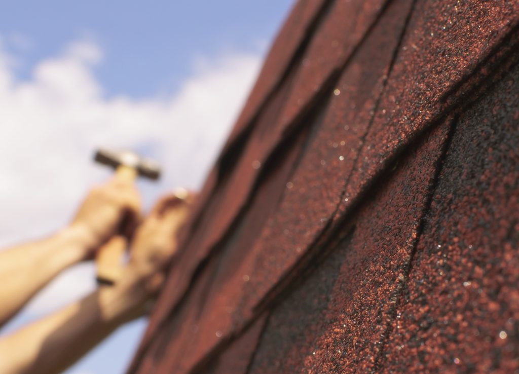 unfocused hands repairing a roof with red shingles in the forefront, focused