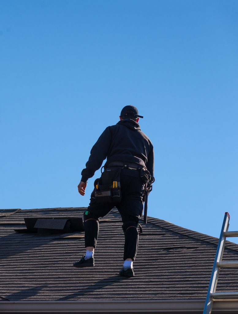Roofer evaluating roof for roof restoration vs roof replacement