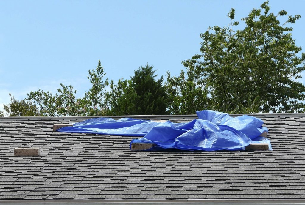 picture of roof wind damage covered by a tarp held down with rocks