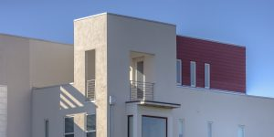 Modern red and white home with flat roof and balcony.