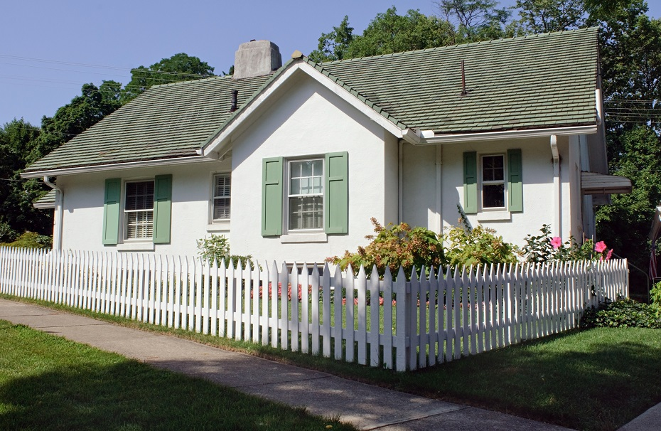 Small house with a sloped roof and white picket fence. It looks wholesome and pleasant.